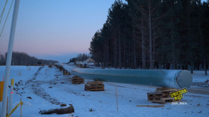 Line 3 Pipeline lifted off the snowy ground by wooden pallets at dusk