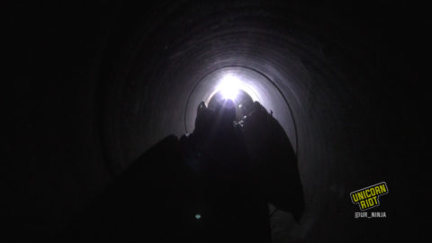 Three people inside a dark pipeline slightly illuminated by a headlamp