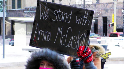 "Sign reads ""we stand with Amina McCaskill"""
