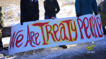 """Water Protectors holding banner that says, """"We Are Treaty People."""""""