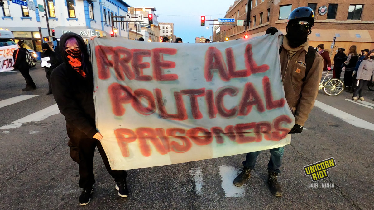 banner reading 'free all political prisoners' was held while housing activists blocked Hennepin Ave