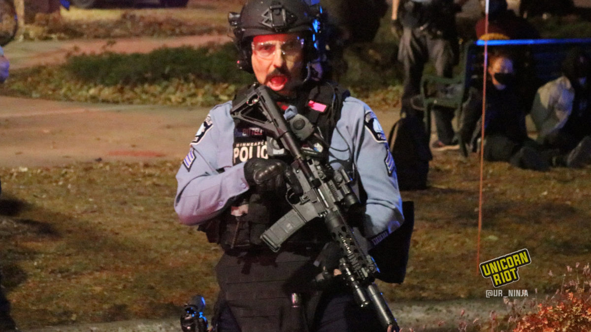 Sergeant Andrew Bittell holding an assault rifle as MPD officers make arrests during an election night dance party