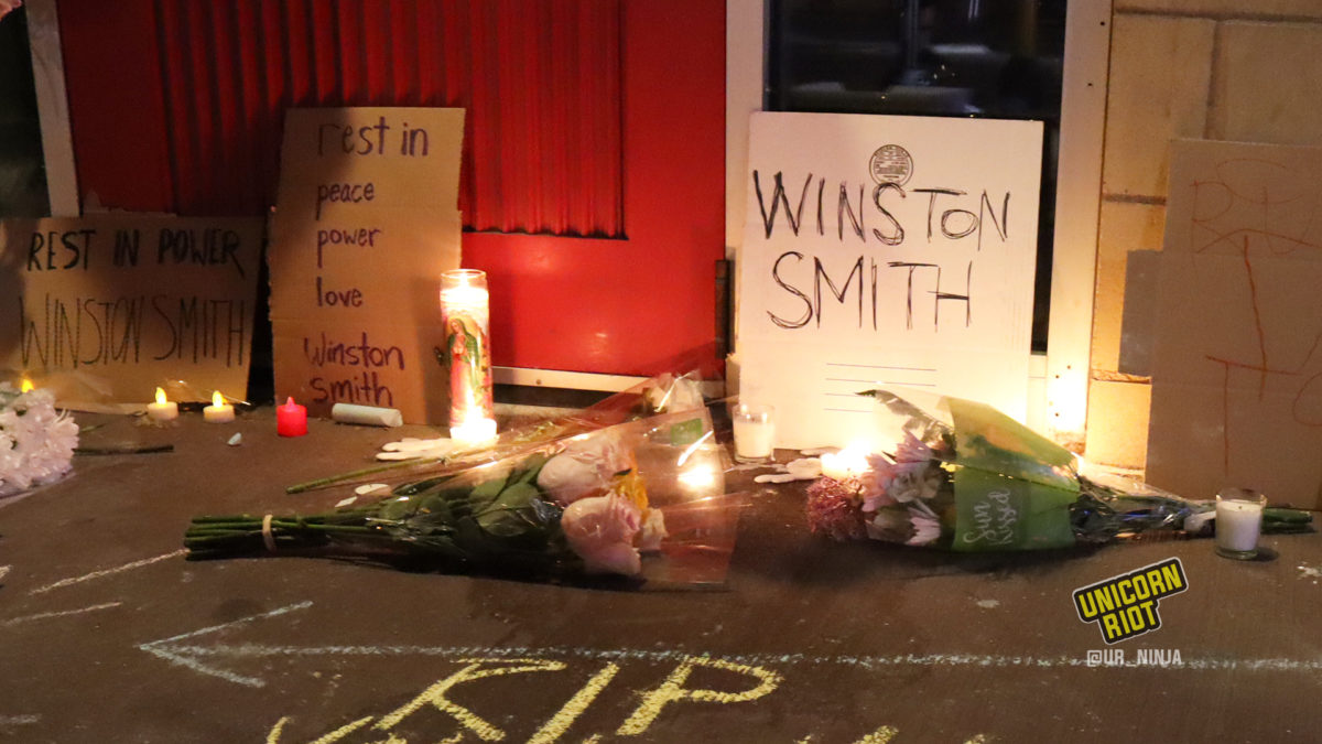 Flowers and signs placed on the sidewalk near the parking ramp where Smith was killed - June 4, 2021