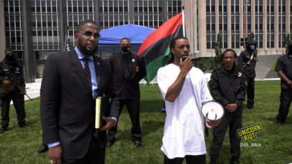 Corey, Dorian Murrell's cousin speaks into megaphone while standing next to family attorney Malik Shabazz and in front of a formation of Black Panther members, some of whom are armed