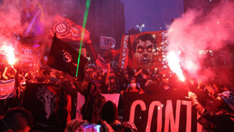 large street protest in sao paulo showing flares lit, lazers shining and large signs against brazilian president bolsonaro