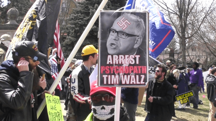 "sign saying ""arrest psychopath tim walz"" with swastika on walz image"